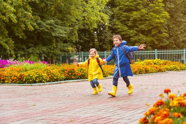 Happy children laugh, rush and run to school dressed in raincoats