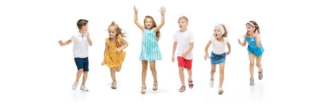 행복한 아이들, 작고 감정적인 백인 아이들이 흰색 배경에 격리되어 점프하고 달리고 있습니다. 행복하고 명랑하고 성실해 보입니다. 광고에 대 한 copyspace입니다. 어린 시절, 교육, 행복 개념입니다.