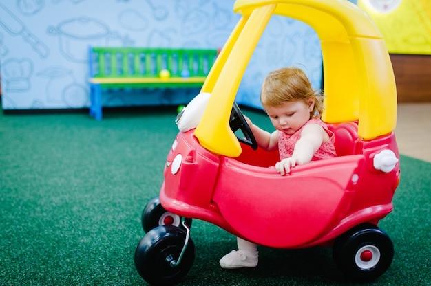 Счастливые дети маленькая девочка ребенок едет на красной большой машине по дороге крупным планом ребенок ведет машину