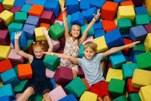 Счастливые дети лежат в мягких кубиках, детская площадка в развлекательном центре.