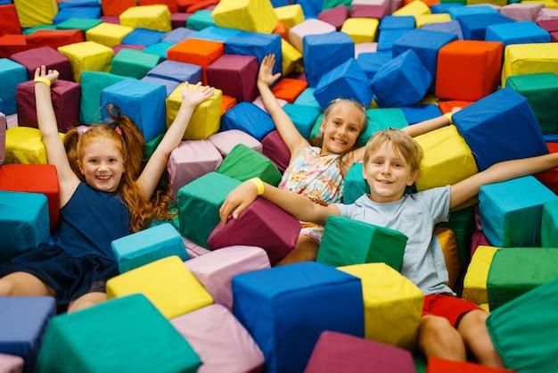 Счастливые дети лежат в мягких кубиках, игровая комната
