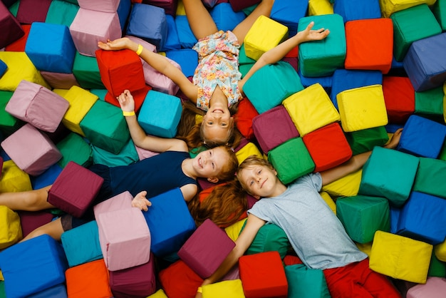 Happy children lying in soft cubes, playroom