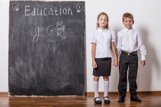 Счастливые дети начальной школы в классной настенной доске