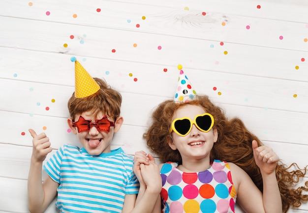 Счастливые дети на карнавальной вечеринке, лежа на деревянном полу. счастливое детство, концепция праздника.