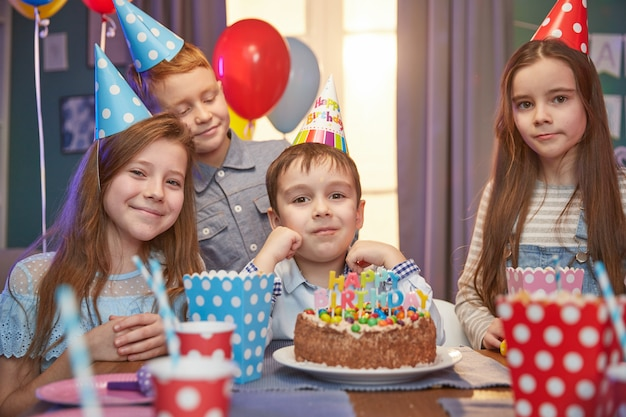 Happy children in party caps celebrating a birthday