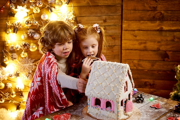 Happy children in a plaid with christmas gingerbread in a decorated room for the holiday.