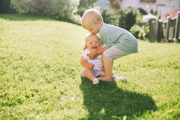 幸せな子供たちは屋外で自然で遊ぶ兄と妹は夏の外で一緒に楽しんでいます