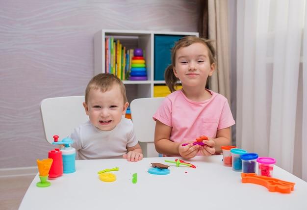 幸せな子供たちは部屋のテーブルで粘土で遊ぶ