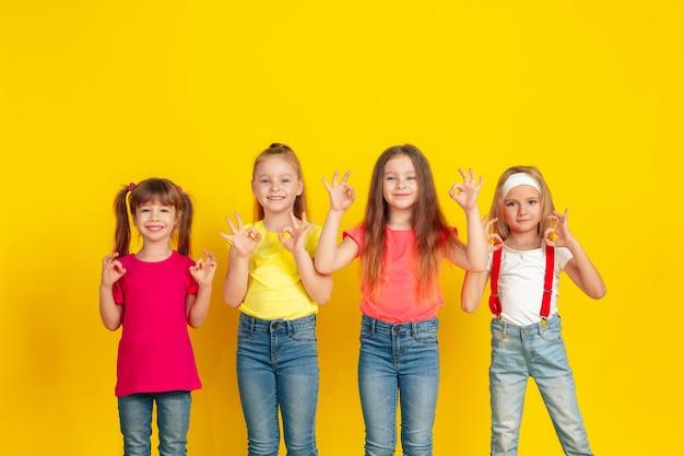 Счастливые дети играют и веселятся вместе на желтой стене
