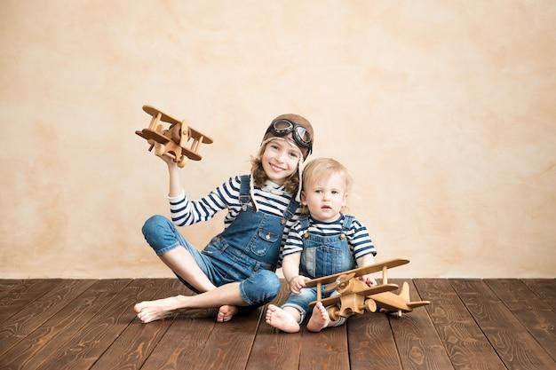 집에서 놀고 행복한 아이들. 아기 소년과 소녀 장난감 비행기