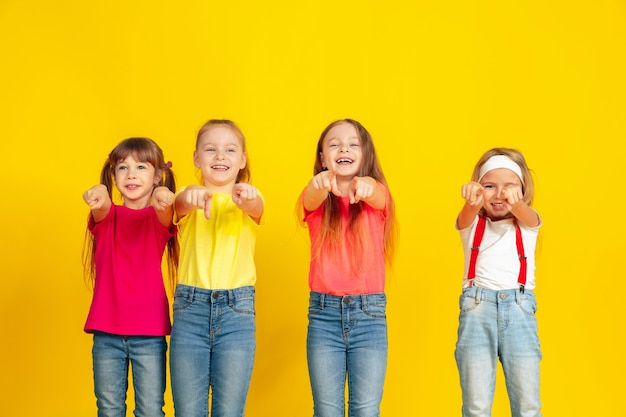 Happy children playing and having fun together on yellow  wall