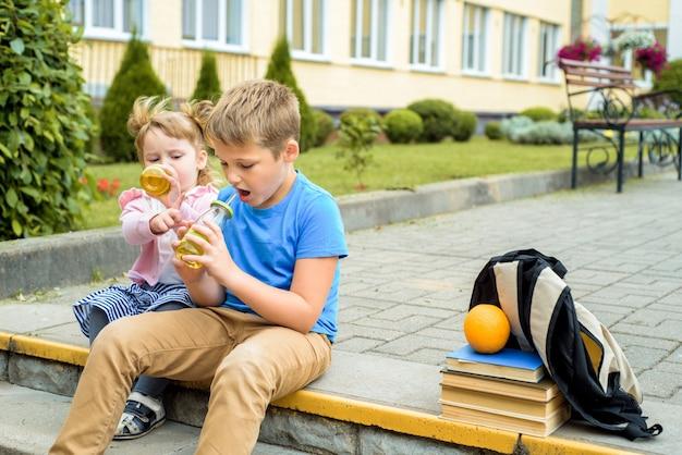 낮 시간에 학교 운동장에서 노는 행복한 아이들 학교 아침 식사, 과일 및 주스. 교과서, 책의 스택. 행복하고 친절한 여동생