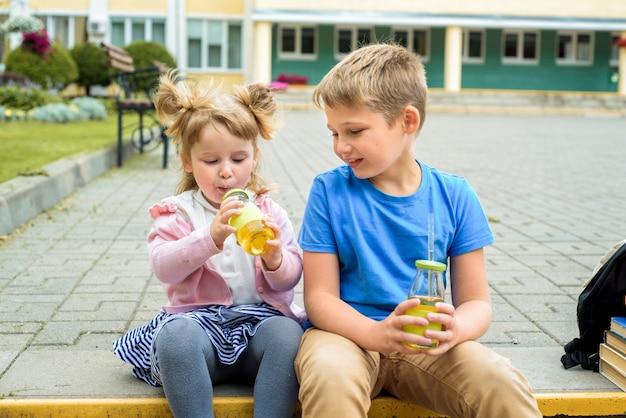 Счастливые дети играют в школьном дворе в дневное время.