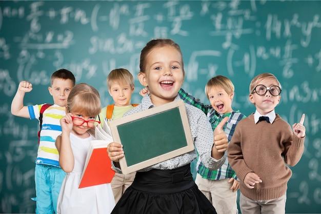 黒板の背景でポーズをとって幸せな子供たち