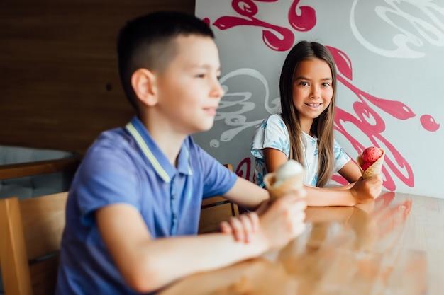 Счастливые дети отдыхают с мороженым в руках в кафе в один летний день вместе.