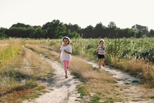 自然の中で夏に牧草地で走っている幸せな子供たち。
