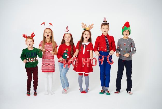 Bambini felici che cantano canti natalizi