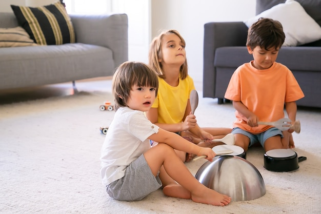 Happy children sitting on carpet and playing with utensils. cute caucasian little boys and blonde girl having fun together in living room and knocking on pans. childhood and home activity concept