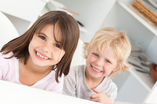 Happy children sitting at a table in the kitchen