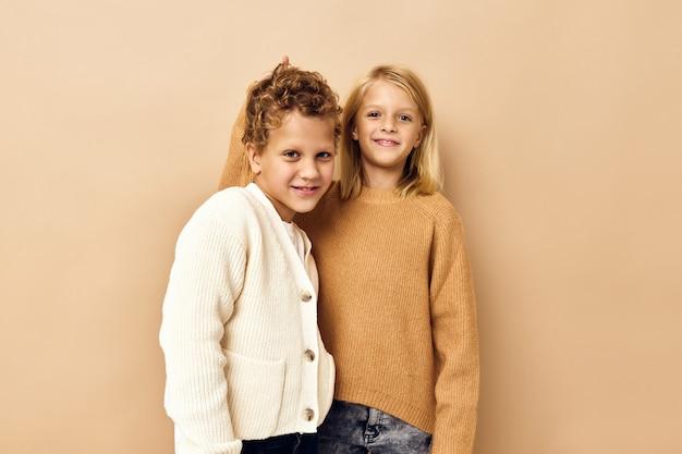 幸せな子供たちが笑顔でカジュアルな服のスタジオの感情でポーズをとる