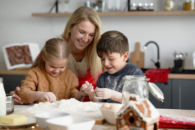 Счастливые дети проводят время на кухне с мамой