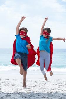 Happy children in superhero costume at beach