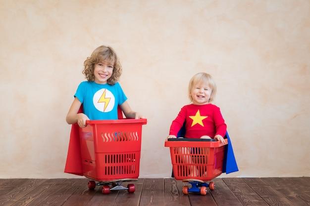家で遊ぶ幸せな子供たちのスーパーヒーロー。