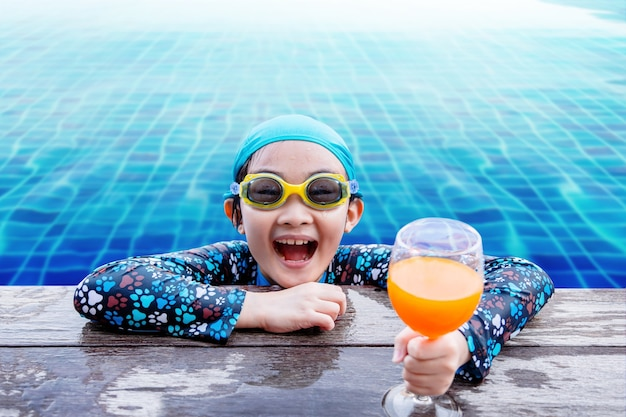 Happy children at the swimming pool side, girl relaxing with summer drink