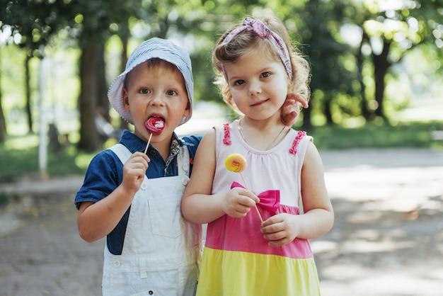 Happy children taste candy on a stick