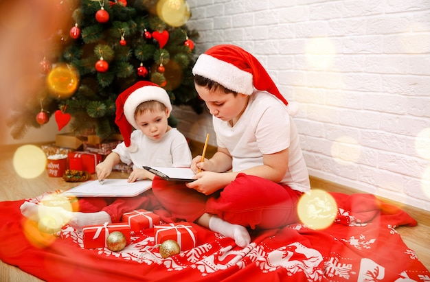 Счастливые дети думают о его подарках для них с рождеством