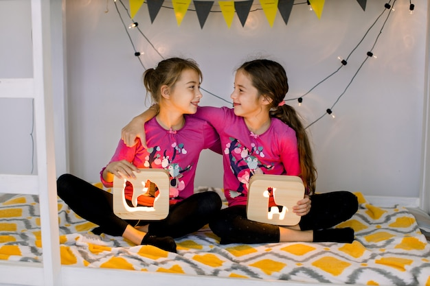 Happy children, two cute 10 year old girls sisters, in child's room on a bunk-bed, sitting in lotus position, looking each other and holding wooden night lamps with cut out pictures.
