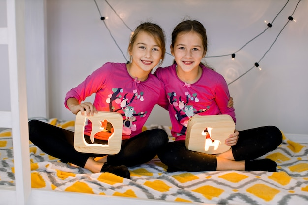 Happy children, two smiling cute 10 year old girls sisters, in child's room on a bunk-bed, sitting in lotus position and holding wooden night lamps with cut out pictures.