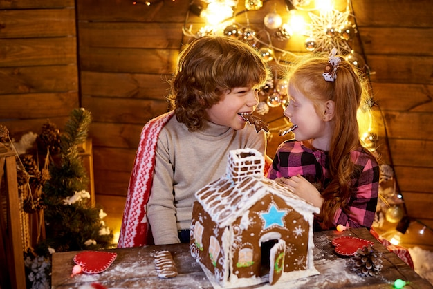 Happy children with christmas gingerbread in a decorated room to the holiday.
