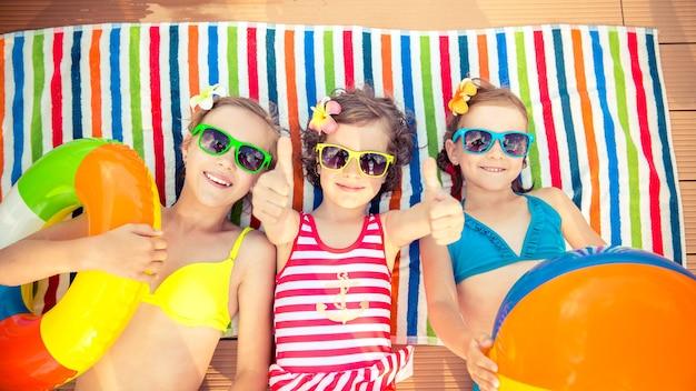 カラフルな剥き出しのビーチタオルの上に膨らませて置くカラフルなサングラスで幸せな子供たち