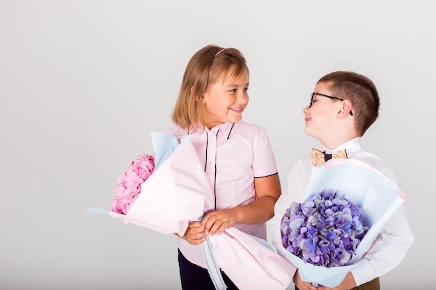 白い背景の上の花を持つ幸せな子供