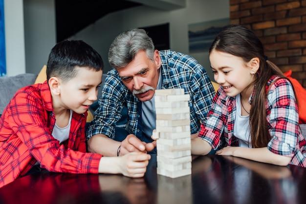Счастливые дети с дедушкой играют в деревянные кубики дома