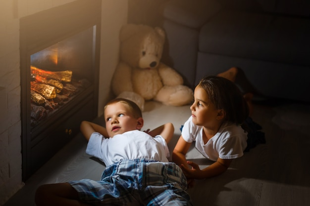 Happy children with magic at home near fireplace