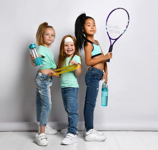 스포츠 장비 스튜디오와 함께 행복 한 어린이 흰색 배경에 고립 된 초상화를 쐈 어. 청바지를 입은 다민족 소녀, 낚시를 좋아하는 티셔츠에 물병, 큰 테니스 라켓, 피트니스 고무