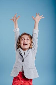 그녀의 손으로 행복한 차일드가 푸른 배경에 고립된 승리를 즐기며 자랐다