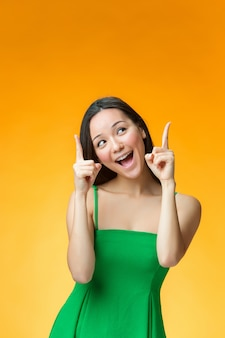 The happy chinese girl on yellow background
