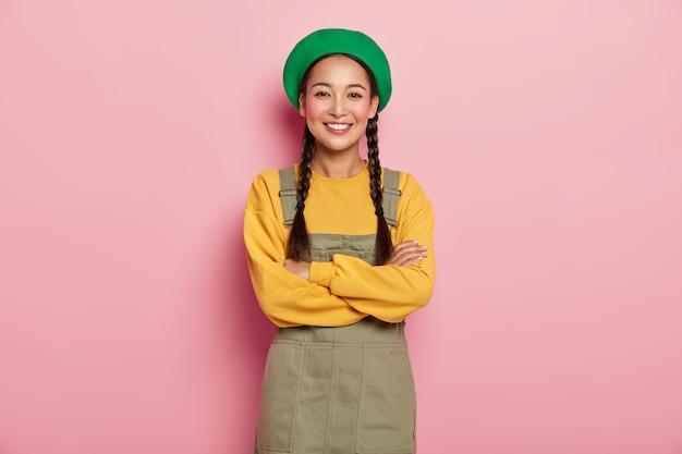 행복한 중국 밀레 니얼 소녀는 팔짱을 끼고 카메라를 향해 즐겁게 웃으며 남자 친구와 즐거운 대화를 나누며 녹색 베레모를 입고 노란색 스웨트 셔츠를 입습니다.