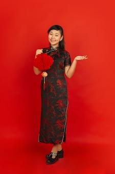 ハッピーチャイニーズニューイヤー2020。赤い背景で隔離のアジアの若い女の子の肖像画。伝統的な服を着た女性モデルは、装飾で幸せで笑顔に見えます。お祝い、休日、感情。