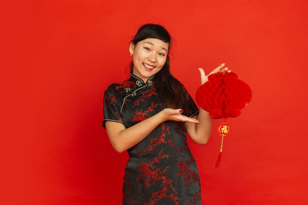 Happy chinese new year 2020. asian young girl's portrait isolated on red background. female model in traditional clothes looks happy and smiling with decoration. celebration, holiday, emotions.