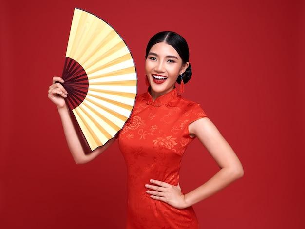 해피 중국 설날. 빨간색 배경에 고립 된 팬을 들고 전통적인 치파오 qipao 드레스를 입고 아시아 여자.