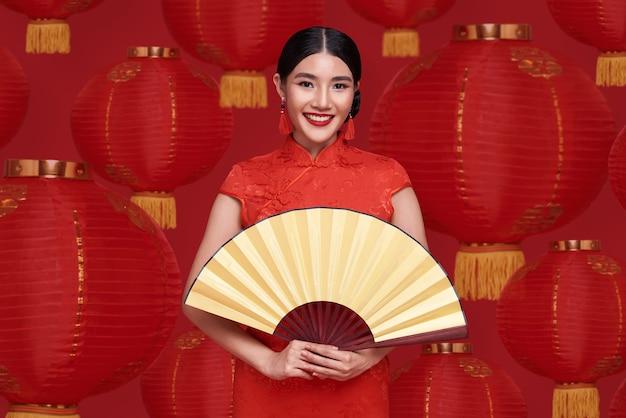Счастливого китайского нового года. азиатская женщина в традиционном платье cheongsam qipao, держащая вентилятор на китайской лампе.