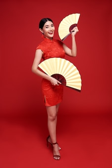 Счастливого китайского нового года. азиатская женщина в традиционном платье ципао cheongsam, держащая вентилятор на красном.