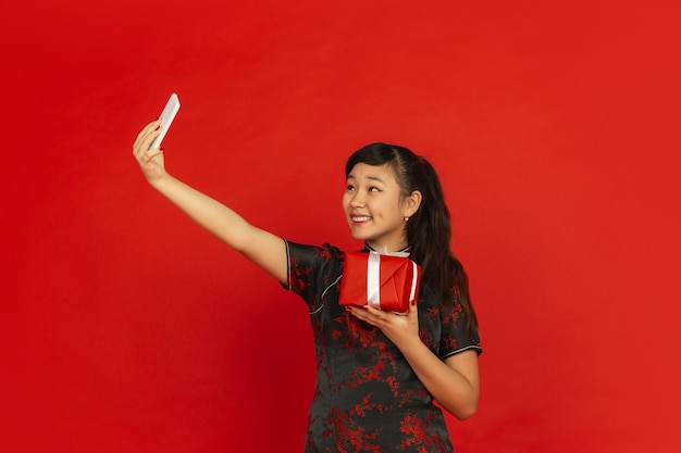 Happy chinese new year. asian young girls's portrait isolated on red background