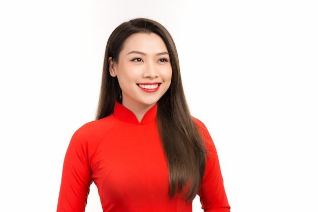 幸せな中国の旧正月 クラシックなビンテージ スタイルの笑顔で赤いベトナムの伝統的なドレスを着ている美しいアジアの女性