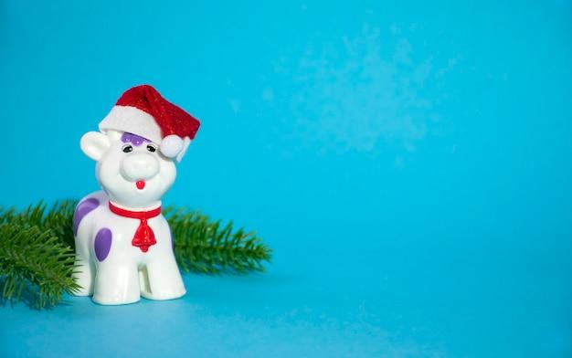 2021年のシンボルとして緑のモミの枝と赤いサンタの帽子の幸せなクリスマスの雄牛または牛のおもちゃ
