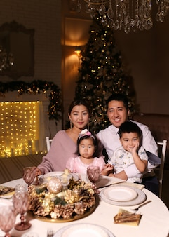 Happy christmas dinner, asian family with children smiling by the fireplace and christmas tree